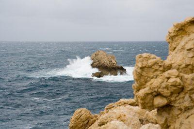 ein Felsen im Meer an dem Wellen brechen
