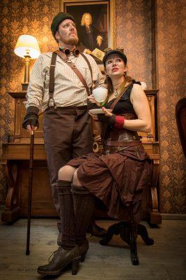 Portrait eines stehenden Mannes und einer sitzenden Frau mit Teetasse