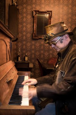 Mann mit Zylinder spielt Klavier