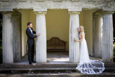 Das Brautpaar steht hinter zwei nebeneinander stehenden Säulen und schaut sich an