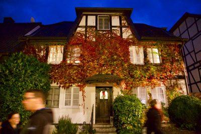 Mit Wein bewachsenes Haus mit hellen Fenstern