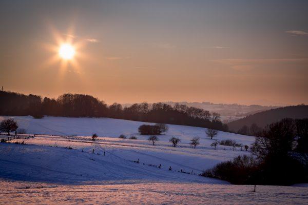Sonnenstern am Abendhimmel über Schneebedeckten Hügeln