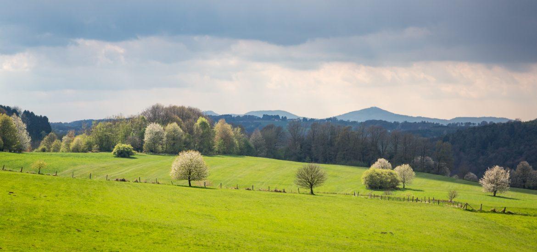 dunkle Wolken über grünen Hügeln